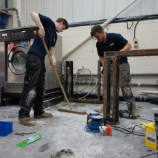 Industrial Laundry Equipment Engineers installing a Washing Machine.